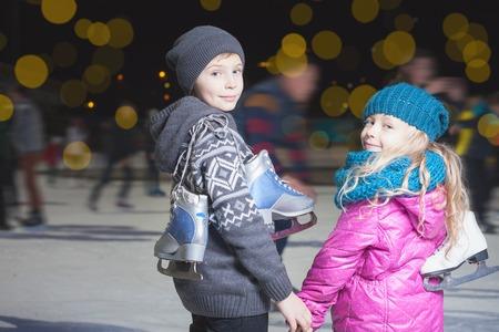 Gelukkige kinderen schaatsen op ijsbaan buiten, in de winter 's nachts, sport en een gezonde levensstijl, schaatsen in Holland. Grappig kind, jongen en meisje, zus en broer. Familie Stockfoto - 50004474