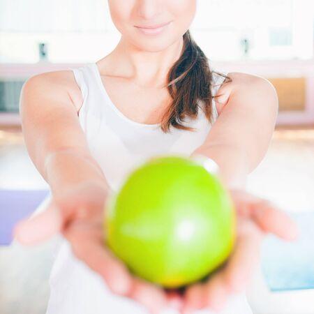 abdomen plano: Primer concepto de estilo de vida saludable con una mujer hermosa vestida de blanco con una gran manzana verde. alimentación vegetariana y la dieta buena para su peso y un vientre plano.