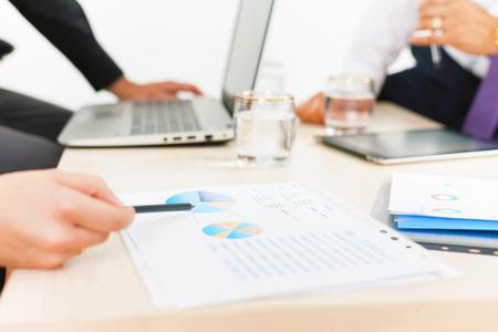 사무실에서 비즈니스 회의 동안 테이블에 근접 그래프 및 차트입니다. 세미나에 대한 재무 성과에 대한 임원 보고서