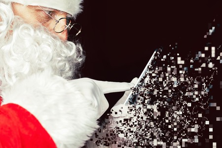 photoshop: Santa Claus using a mobile phone at Christmas time. Santa typing message or sms to Elf or Dwarf. Photoshop, art effect of pixelated decomposition. New Year.