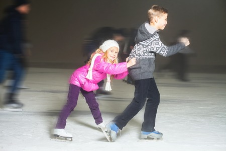 Happy children ice skating at ice rink outdoor, at winter night, sport and healthy lifestyle, ice skating at Holland. Funny kids, boy and girl, sister and brother. Family
