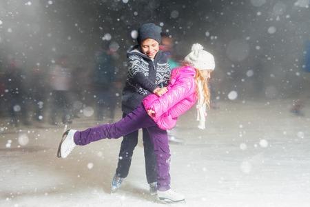 niños felices del patinaje de hielo en la pista de patinaje sobre hielo al aire libre, patinaje artístico, en la noche de invierno cubierto de nieve, el deporte y la vida sana, el patinaje sobre hielo en Holanda. niños divertidos, niño y niña, hermana y hermano. Familia Foto de archivo
