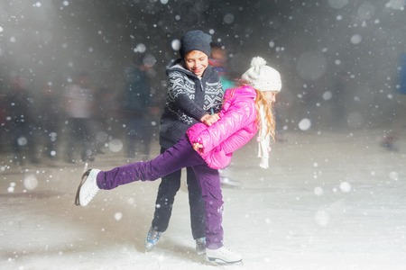 Happy children ice skating at ice rink outdoor, figure skating, at winter snowy night, sport and healthy lifestyle, ice skating at Holland. Funny kids, boy and girl, sister and brother. Family
