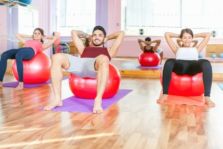 flat stomach: Young people lead a healthy lifestyle, exercise and engaged in fitness room. Using gimnastic ball. Flat stomach, pumping press. Exercise strengthens a person physically and make them more happy! Stock Photo