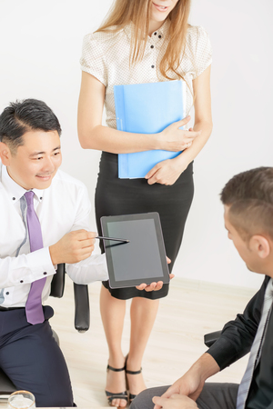 bussinessman: Image of concept of business meeting and conference at office. Asian bussinessman working or using tablet pc computer. There are a multiracial people of asian and caucasian Stock Photo