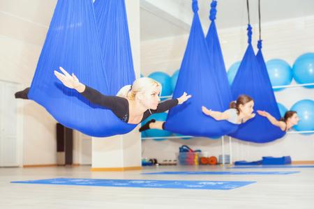 공중 요가 운동이나 실내 반 중력 요가 일을 젊은 여성. 비행, 헬스, 스트레칭, 균형, 운동 및 건강한 라이프 스타일 사람들. 해먹을 사용하는 여자. 스톡 콘텐츠