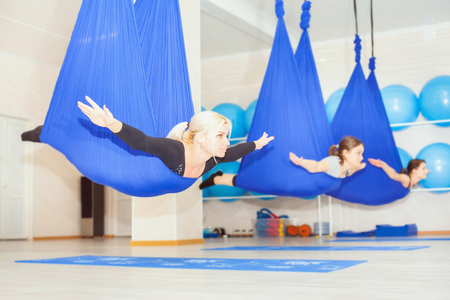 Young women doing aerial yoga exercise or antigravity yoga indoor. Flying, fitness, stretch, balance, exercise and healthy lifestyle people. Woman using hammock. Stock Photo