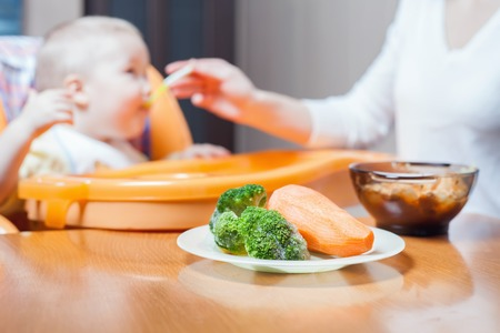 highchair: Mom feeds the baby soup. Healthy and natural baby food. Vegetables, carrots, cabbage, broccoli. ?hild sitting on the highchair at the table. Stock Photo