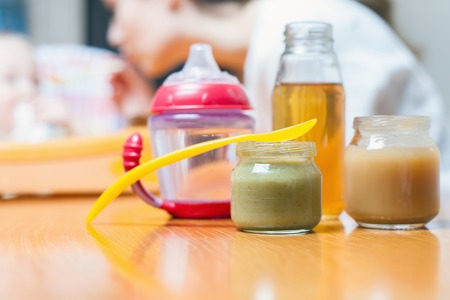nursing bottle: Healthy and natural baby food of vegetables, carrots, cabbage, broccoli and apple juice at bottle. Diet. Group objects. Feeding cup. Mother care and love for her baby.