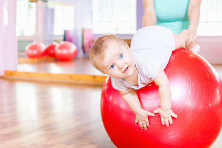 Mother with happy baby doing exercises with red gymnastic ball at fitness class. Concept of caring for the babys health.