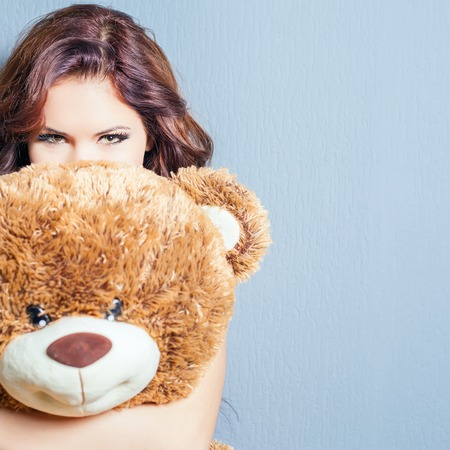 lady s: Happy woman received a teddy bear. Blue background. Her beautiful eyes looking at camera. Concept of holiday, birthday, World Womens Day or Valentines Day, 8 March. Copy space