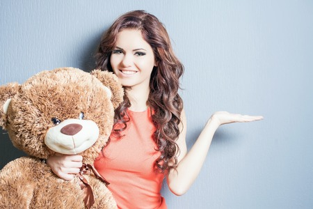 valentine s day teddy bear: Happy woman received a teddy bear. She is pointing at copy space for your design. Looking at camera. Blue background. Concept of holiday, birthday, World Womens Day or Valentines Day, 8 March.