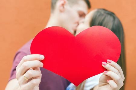 beso: feliz pareja besarse y la celebración de un símbolo del corazón grande en el fondo rojo. Imagen listo para Internacional. Concepto del día de San Valentín, celebración