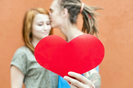 valentine s card: Happy Valentines Day couple holding red heart symbol and kissing, 14th February celebration, Valentine. Love concept.