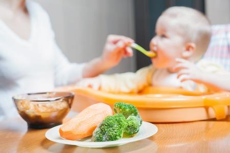 bebe sentado: La mama introduce la sopa bebé. Alimentos para niños sanos y naturales. Verduras, zanahorias, repollo, brócoli. Niño sentado en la silla en la mesa.