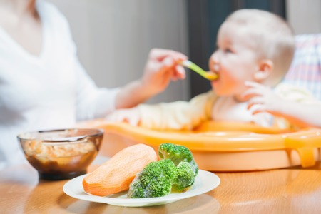 mum and baby: Mom feeds the baby soup. Healthy and natural baby food. Vegetables, carrots, cabbage, broccoli. Child sitting on the highchair at the table.