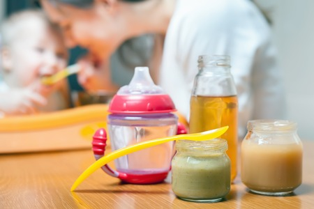 Healthy and natural baby food of vegetables, carrots, cabbage, broccoli and apple juice at bottle. Diet. Group objects. Feeding cup. Mother care and love for her baby.