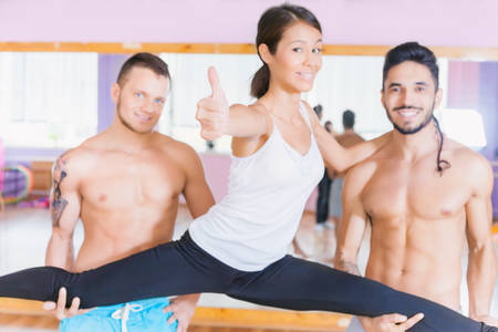split up: Young beautiful asian woman with thumbs up gesture doing split and stretching between two handsome guys. Exercise of fitness and healthy lifestyle strengthens a person physically and make them more happy! Stock Photo