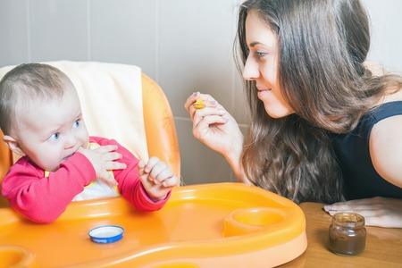 highchair: Mom feeds the baby puree. Healthy and natural baby food. Vegetables, broccoli. Child sitting on the highchair at the table. Stock Photo