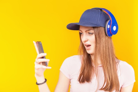 Surprised teenage girl uses a headphones and mobile phone.