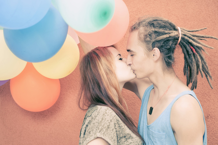 s day: Young happy couple kissing and holding balloons.
