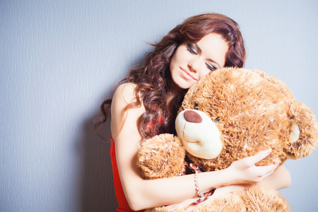 womens day: Happy woman received a teddy bear. Blue background. Her beautiful eyes looking at camera. Concept of holiday, birthday, World Womens Day or Valentines Day, 8 March. Copy space