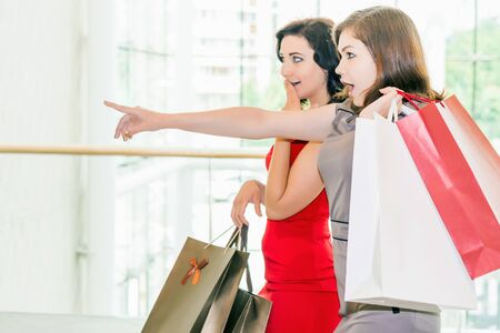 sell out: Happy fashion women with bags talking about buying or new dresses or shoes indoor at the shopping center. At the background there is a big window of mall. Square orientation Stock Photo