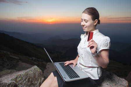 freelancing: Concept of online payment by plastic card through the Internet Banking. Laptop. Holding credit card. Woman is shopping outdoor