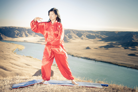 Mature asian woman doing kundalini or Zhan zhuang Qigong yoga. Kundalini is term for spiritual energy, life force located at base of spine. Based on movement of internal energy, system of channels, energy centers, chakras
