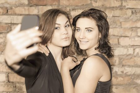 girl friend: Two happy and funny girls make selfie on mobile phone. They are now a party or birthday, and celebrate fun!