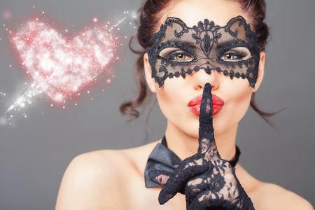 Sexy woman with carnival mask. Fashion. Venetian carnival. Sex shop. Hot babe. Party. Love symbol. Conceptual image of love and safe sex with contraceptive