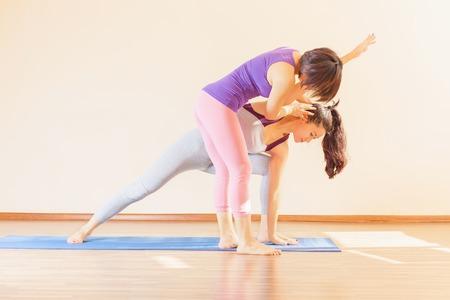 アジアのトレーナーは、屋内、ヨガのクラスで個々 のヨガのクラスを行っています。健康的なライフ スタイルと生活に適切な態度の概念
