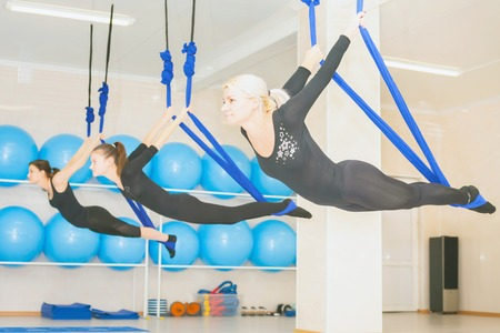 hammock: Young women doing aerial yoga exercise or antigravity yoga indoor. Flying, fitness, stretch, balance, exercise and healthy lifestyle people. Woman using hammock. Stock Photo