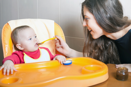 highchair: Mom feeds the baby soup. Healthy and natural baby food. Vegetables, carrots, cabbage, broccoli. Child sitting on the highchair at the table.