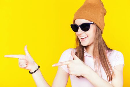 Funny teenage girl dressed in sunglasses and hat. Pointing left. Fashion student. Cool girl. Shopping. Color Stock Photo