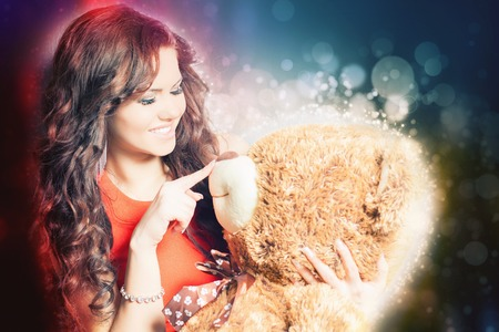 women  s fashion: Happy woman received a teddy bear. Blue background. Concept of holiday, birthday, World Womens Day or Valentines Day, 8 March. Digital effect. Blur