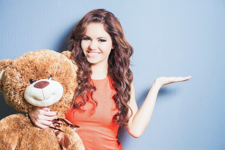 women  s fashion: Happy woman received a teddy bear. She is pointing at copy space for your design.