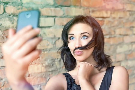 Young pretty girl making selfie of her mustache hair. She is now a party or birthday, and celebrate fun!