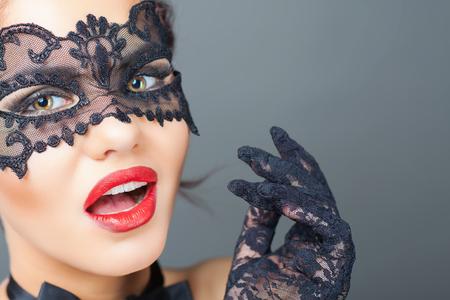 Mujer sorprendida atractiva del primer con la máscara del carnaval. Moda. Carnaval veneciano. Sex shop. Bebé caliente. Fiesta. fondo de la noche