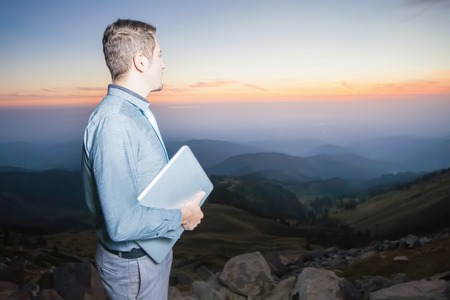businessman thinking: Image of a businessman on the top of the mountain, holding laptop. He thinking about future plans. At the background there are beautiful panorama of valley with high peaks and beautiful sunset