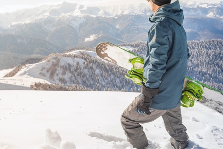 Closeup adventure to winter sport. Snowboarder man hiking at mountain. Looking for powder to freeride. Stock Photo
