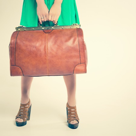 dimensions: Closeup woman holding hand luggage at the airport terminal. Suitcase sale. Tourism. Vintage tourist bag. Passenger. Airlines. Weight and baggage dimensions. Baggage allowance Stock Photo