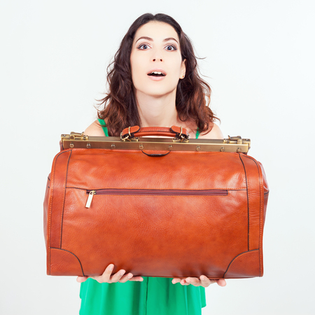 dimensions: Surprised woman holding hand luggage at the airport terminal. Suitcase sale. Tourism. Vintage tourist bag. Passenger. Airlines. Weight and baggage dimensions. Baggage allowance