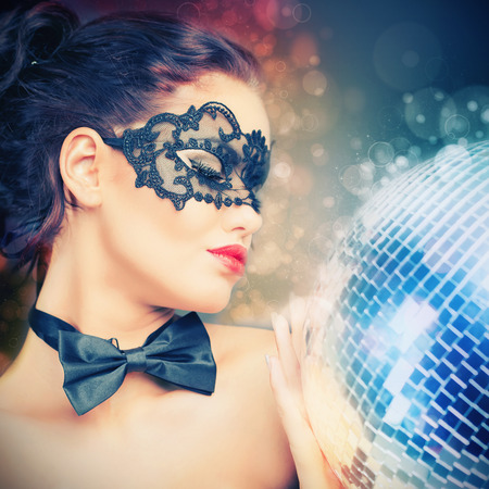 cool background: Young sexy woman in carnival mask keeping disco ball. Party. Night club. Fashion. Venetian carnival. Stock Photo