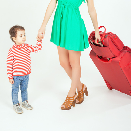 little boy and girl: Child with mother ready to travel to Europe, Italy. Travel insurance. Family carries luggage at white background. Airport terminal. Suitcase. Traveler girl dressed in summer green dress. Tourism. Tourist bag. Stock Photo