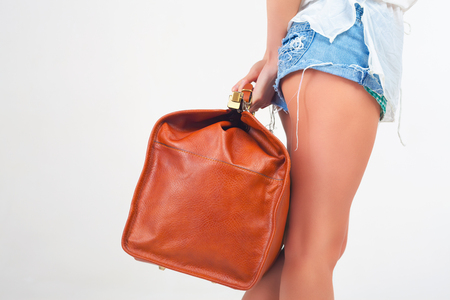 allowance: Closeup woman holding hand luggage at white background. Vacation rentals, packages. Airport terminal. Leather suitcase sale. Tourism. Vintage tourist bag. Weight, baggage dimensions. Baggage allowance