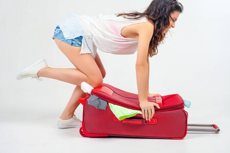'young things': Young woman packs her things, clothes at full luggage, baggage, suitcase. Journey, vacation. Summer travel. Luggage dimensions and weight. Tourist bag. Passenger. Airlines. Stock Photo