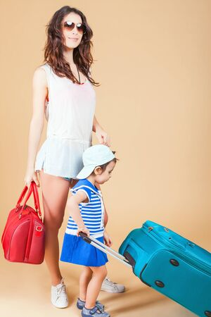 rentals: Child with mother ready travel to Europe, Italy. Family carries luggage at white background. Vacation rentals, packages. Airport terminal. Suitcase. Tourism. Tourist bag. Stock Photo