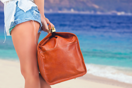 Closeup woman holding hand luggage. Summer travel. Blue sea and white sandy beach at Bali. Vacation rentals. Airport. Terminal. Leather suitcase sale. Tourism. Vintage tourist bag.