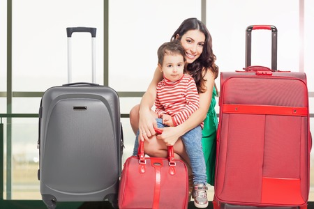 rentals: Child with mother ready to travel. Airport terminal. Travel insurance. Family carries luggage. Vacation rentals, packages. Suitcase. Tourism. Tourist bag.